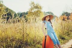 带着单独旅行暑假的橙色手提箱的愉快的儿童女孩 去夏令营的孩子 免版税库存图片