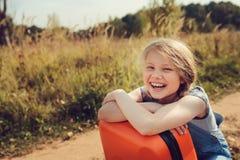 带着单独旅行暑假的橙色手提箱的愉快的儿童女孩 去夏令营的孩子 免版税图库摄影