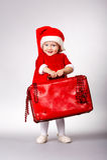带着圣诞节手提箱的小逗人喜爱的女孩 免版税库存照片