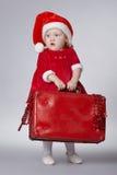 带着圣诞节手提箱的小逗人喜爱的女孩 库存照片