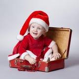 带着圣诞节手提箱的小逗人喜爱的女孩 库存图片