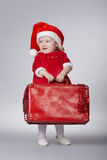 带着圣诞节手提箱的小逗人喜爱的女孩 图库摄影