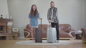 带着大手提箱的愉快的smilling的夫妇身分在家 年轻有胡子的人和年轻美女准备好 股票录像
