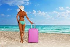 带着大桃红色手提箱的被晒黑的女孩在海滩 免版税库存图片