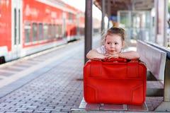 带着大红色手提箱的小女孩在一个火车站 免版税图库摄影