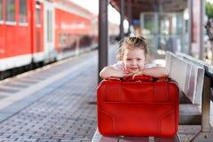 带着大红色手提箱的小女孩在一个火车站 库存照片