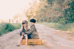 带着大黄色手提箱的两个孩子在减速火箭的样式的路 免版税库存照片
