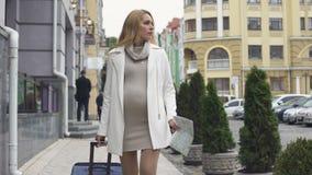 带着寻找诊所的手提箱的可爱的期望的女性在城市,旅行 影视素材