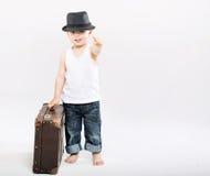 带着巨大的手提箱的小绅士 库存照片