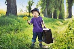 带着巨大的手提箱的年轻男孩 免版税库存照片