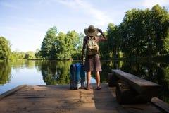带着手提箱的一个旅客在水库的岸站立 免版税图库摄影