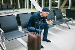 带着手提箱的一个年轻人在机场候诊室坐并且使用一个手机 夜间飞行,调动,等待在 库存照片