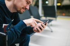 带着手提箱的一个年轻人在机场候诊室坐并且使用一个手机 夜间飞行,调动,等待在 免版税库存照片