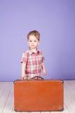 继续带着手提箱的一次旅途的小男孩 免版税库存照片