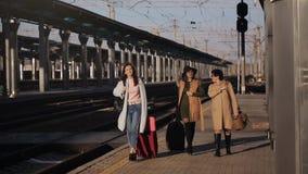 带着手提箱的三名妇女在火车站和谈的平台去 股票录像