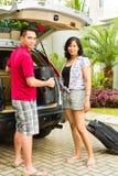 带着手提箱的亚洲夫妇装箱汽车为节假日 免版税库存照片