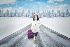 带着手提箱的俏丽的妇女在雪道 免版税图库摄影