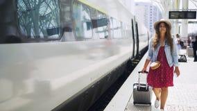 带着手提箱的俏丽的妇女走在火车平台的 股票视频