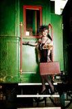 带着手提箱的减速火箭的女孩在老火车附近。 免版税库存图片