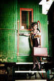 带着手提箱的减速火箭的女孩在老火车附近。 库存照片