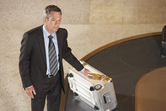 带着手提箱的商人在行李转盘在机场 免版税图库摄影