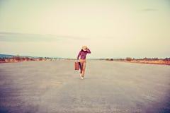 带着手提箱的妇女奔跑 库存照片