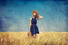 带着手提箱的孤独的女孩在国家(地区)。 在老颜色图象s的照片 库存图片