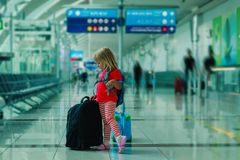带着手提箱的小女孩在机场,家庭度假旅行 库存照片