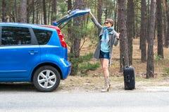 带着手提箱的少妇在森林公路搭车 免版税库存照片