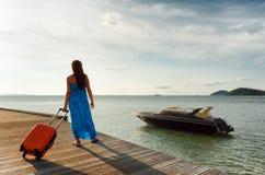 带着手提箱的少妇在码头 免版税库存图片