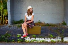 带着手提箱的少年女孩 使布赖顿椅子日甲板英国节假日懒人海边有风夏天的星期日靠岸 库存照片