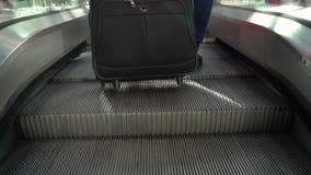 带着手提箱的年轻女人走到自动扶梯的 股票视频
