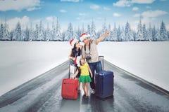 带着手提箱的年轻家庭在多雪的高速公路 库存图片