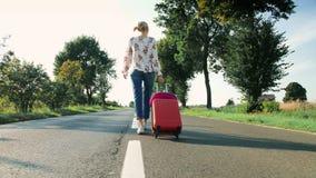 带着手提箱的快乐的女孩走在路的 股票录像