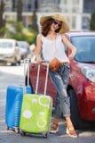 带着手提箱的愉快的女性游人在汽车附近 免版税库存图片