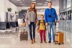 带着手提箱的愉快的家庭在机场 免版税库存照片