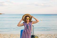 带着手提箱的愉快的旅客妇女在海滩 旅行,旅途,旅行的概念 免版税库存照片