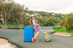 带着手提箱的愉快的旅客妇女在海滩 旅行,旅途,旅行的概念 库存图片