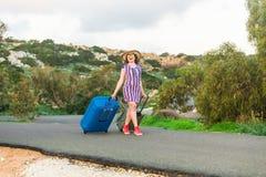 带着手提箱的愉快的旅客妇女在海滩 旅行,旅途,旅行的概念 免版税库存图片
