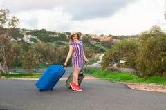 带着手提箱的愉快的旅客妇女在海滩 旅行,旅途,旅行的概念 库存照片
