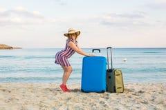 带着手提箱的愉快的旅客妇女在海滩 旅行,旅途,旅行的概念 免版税图库摄影