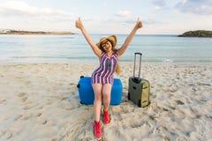 带着手提箱的愉快的笑的妇女游人在海附近 旅行和暑假概念 免版税库存图片
