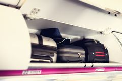 带着手提箱的手行李隔间在飞机 在飞机架子顶部的随身携带的行李  与拷贝的旅行概念 免版税图库摄影