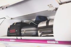 带着手提箱的手行李隔间在飞机 在飞机架子顶部的随身携带的行李  与拷贝的旅行概念 免版税库存照片