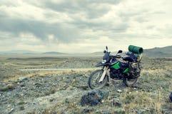 带着手提箱的摩托车单独enduro旅客在石沙漠 免版税库存照片