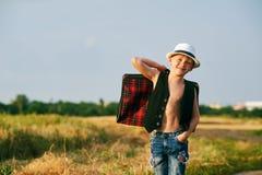 带着手提箱的时髦的男孩在农村路 免版税库存图片