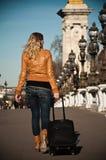 带着手提箱的白肤金发的妇女在亚历山大III桥梁 免版税图库摄影
