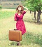 带着手提箱的红头发人女孩在室外。 免版税图库摄影