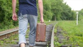 带着手提箱的走在铁路轨道的人的手 影视素材