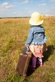 带着手提箱的孤独的女孩。 后面看法 免版税库存图片